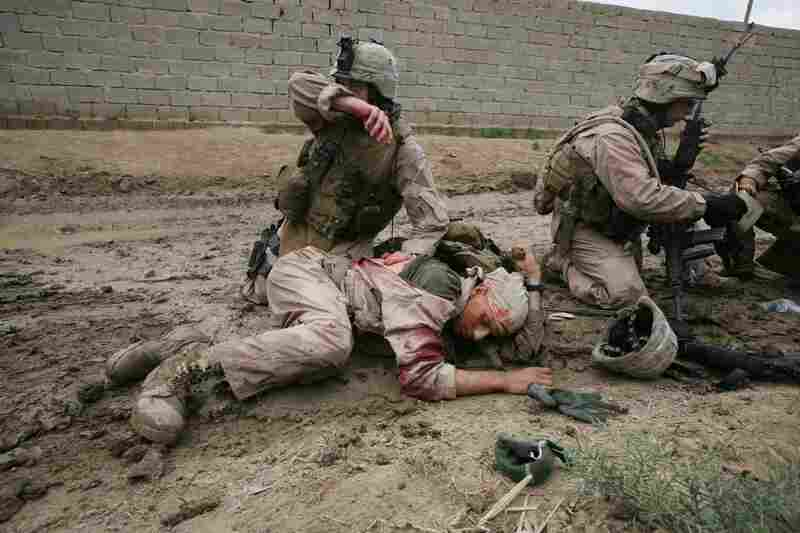 Sgt. Jesse E. Leach assists Lance Cpl. Juan Valdez Castillo after he was shot by a sniper during a joint patrol with the Iraqi Army in Karmah, Anbar Province, Iraq. Valdez was shot through the arm and the right side but survived. 2006