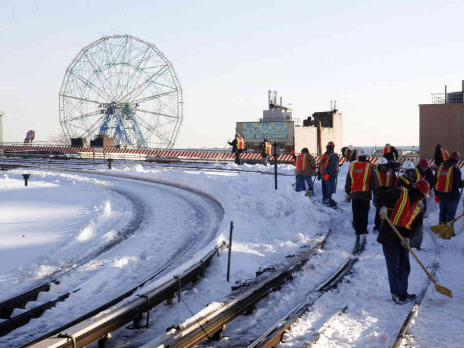 Metropolitan Transportation Authority employees clear snow Tuesday from the Q train track near New York's Coney Island. Although the transportation situation was improving Wednesday in New York, many airline travelers still remain stranded.