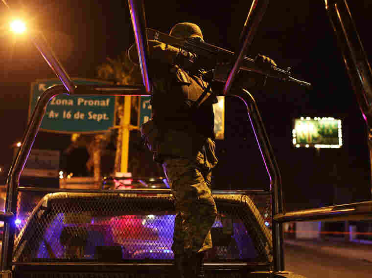 A military police officer watches at the scene of a drug-related murder in Juraez, Mexico.