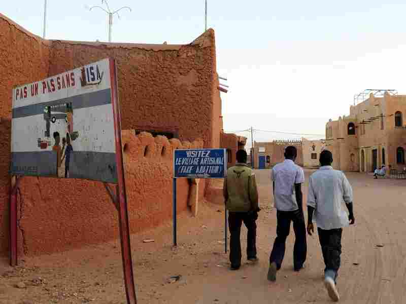 Residents of Agadez, in northern Niger, walk along an empty street.
