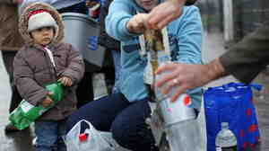 A young child held an empty bottle as people queued to recieve water from a  tap in Belfast on Wednesday.