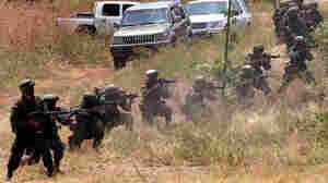 Police officers from different countries fire their weapons at targets during training with Colombia's elite Jungla unit in 2007.