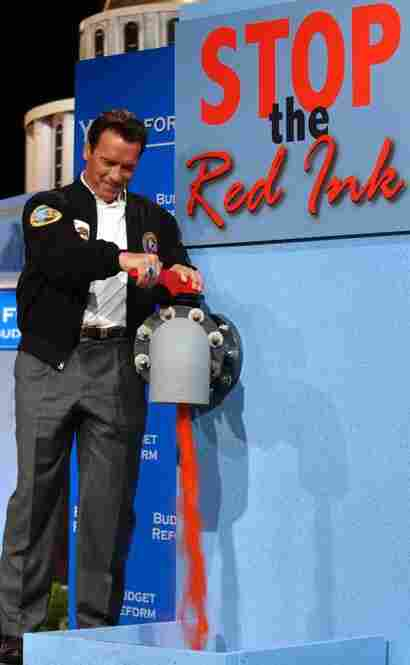 """Schwarzenegger stops the flow of fake red ink during a news conference to discuss cutting state spending in Sacramento. """"The Governator"""" had pledged to fix the state's financial mess, but he leaves behind a $28 billion budget shortfall."""