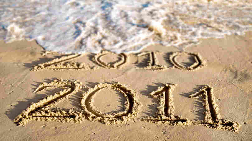 An ocean wave washes away the year 2010 written in beach sand.