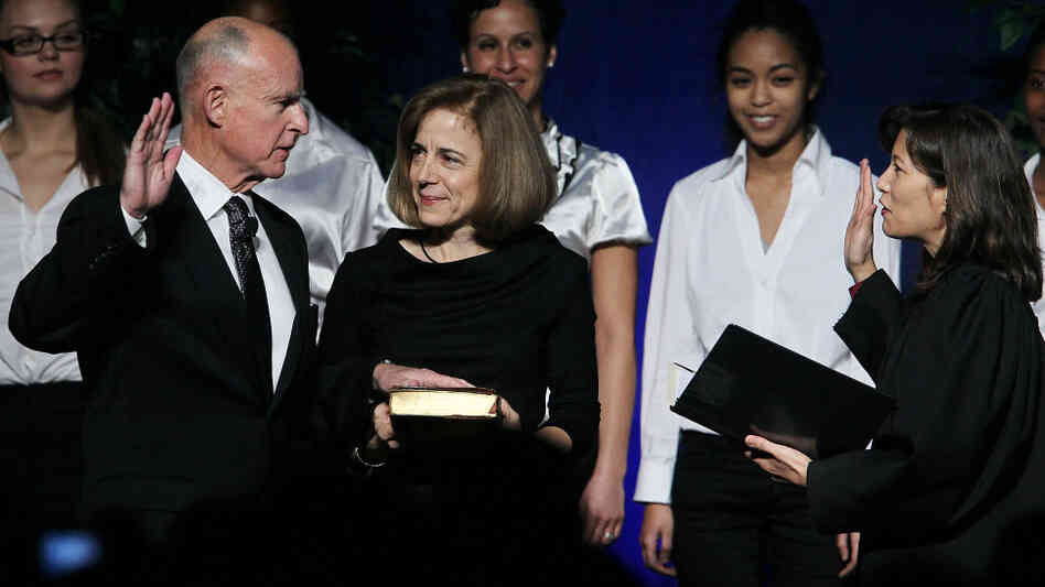 Jerry Brown (left) is sworn in as the 39th governor of California by California Chief Justice Tani CAntil-Sakauye (right) as Brown's wife, Anne Gust-Brown, looks on.
