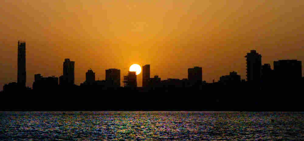 The sun sets over a stretch of the skyline in Mumbai, India.