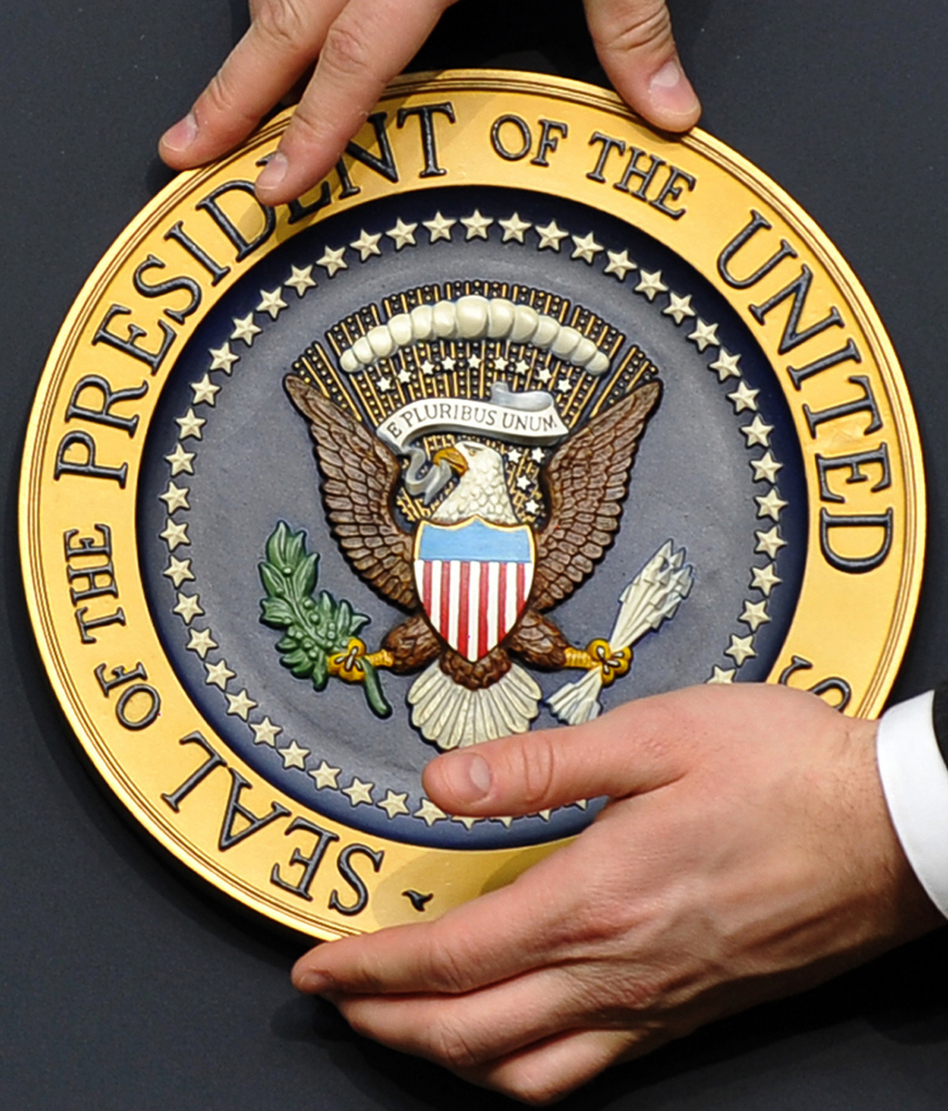 A staff member fixes the presidential seal before President Obama gives a press conference in the Eisenhower Executive Office Building in Washington, D.C., last month.