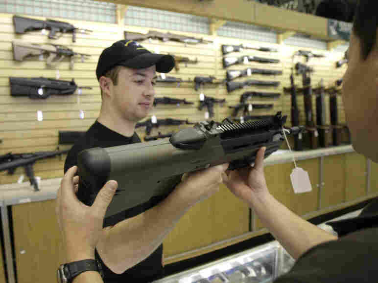 Case Vermillion hands a gun to a customer at the Cheaper Than Dirt gun shop in Fort Worth, Texas, Thursday, Nov. 6, 2008.