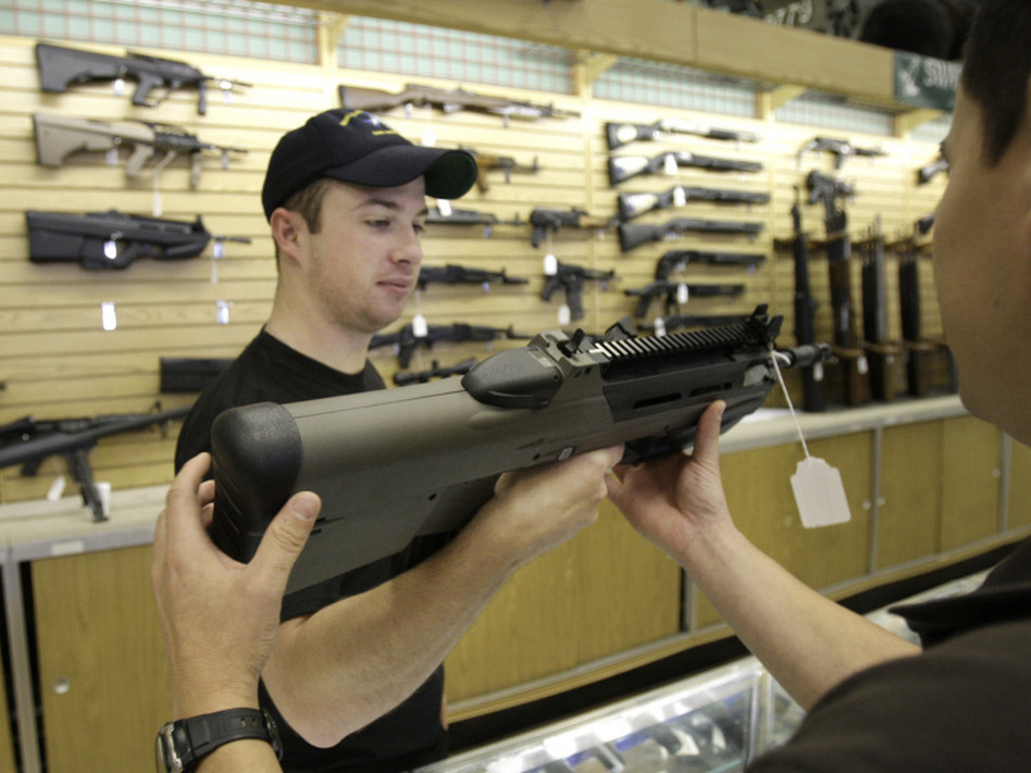 An employee hands a gun to a customer at a gun shop in Fort Worth, Texas. Eight of the top 12 U.S. dealers of guns traced to Mexico are located in Texas.