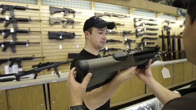 An employee hands a gun to a customer at a gun shop in Fort Worth, Texas. Eight of the top 12 U.S. dealers of guns traced to Mexico are located in Texas. (AP)