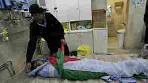 A Palestinian police officer checks the body of a Palestinian woman, Jawaher Abu Rahmah, at a hospital in the West Bank city of Ramallah on Saturday. Palestinian doctors say 36-year-old Abu Rahmah died after inhaling tear gas at a protest against Israel's separation barrier in the village  of Bilin.