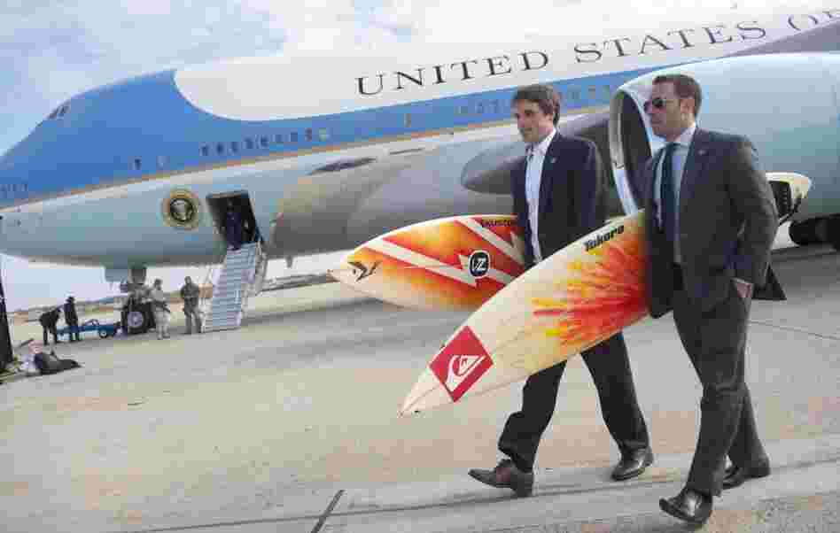 White House staffers Ben Finkenbinder and Nick Shapiro carry surfboards as they walk away from Air Force One after arriving with President Barack Obama at Andrews Air Force Base.