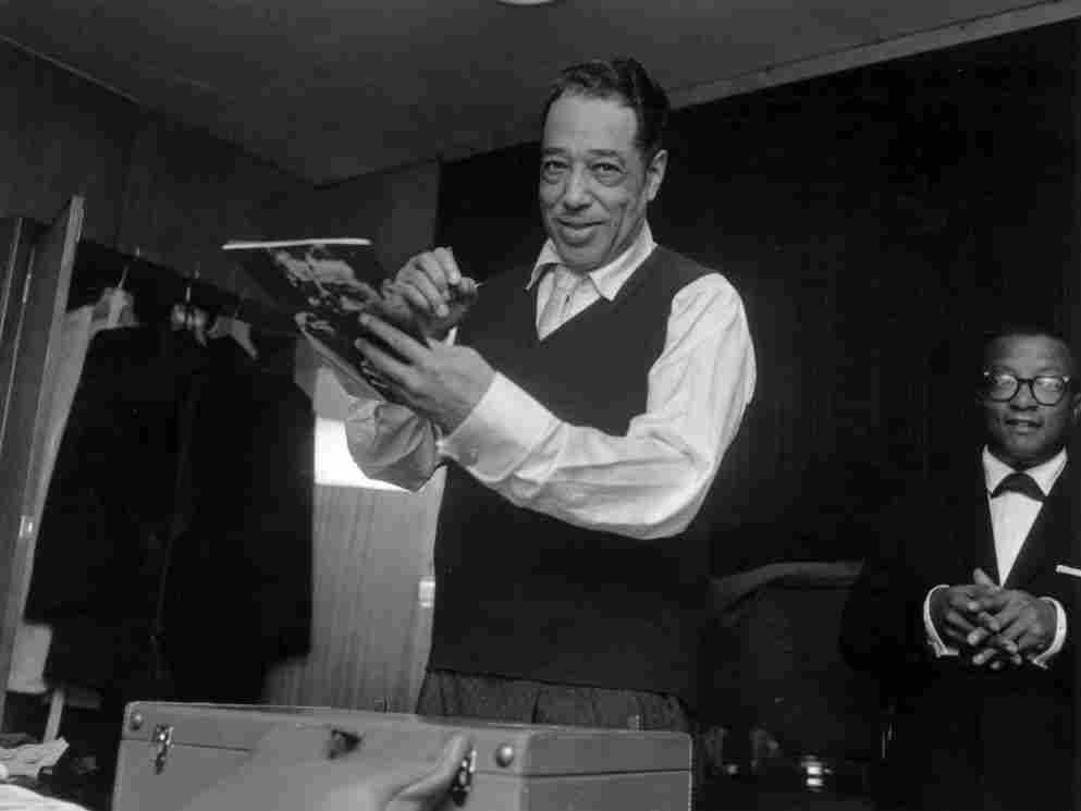 Duke Ellington signs his biography in London in 1958, with Billy Strayhorn in the background.