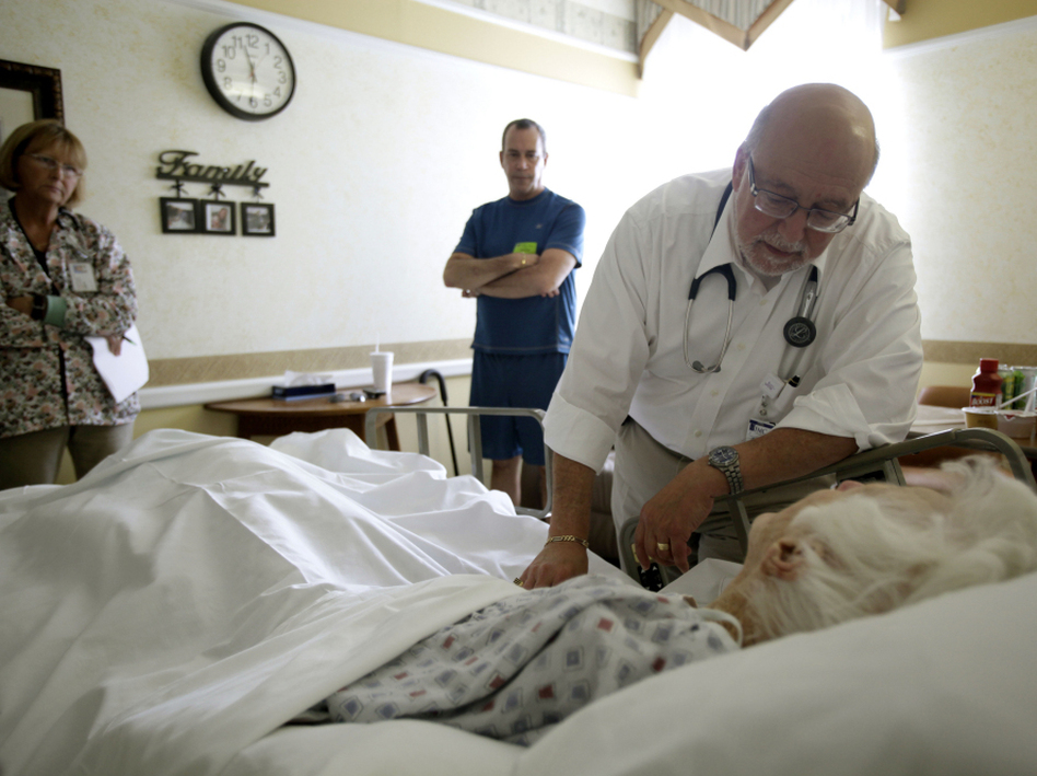 Dr. Joel Policzer checks on Lillian Landry, a patient in the hospice wing of a Florida hospital. Landry made end-of-life decisions to receive little care. (J Pat Carter/AP)