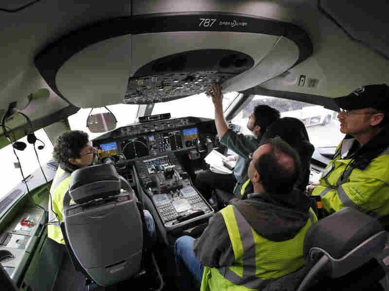 Technicians work in the cockpit of a Boeing 787 at the company's production plant in Everett, Wash. Boeing plans to hire more workers in 2011.