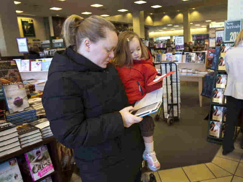 Emily Fernandez, holding her daughter, Bethany, uses her Nook e-reader to browse books at a Barnes & Noble in Hackensack, N.J. The company on Thursday announced its best holiday sales in a decade and credited the Nook for the good news.