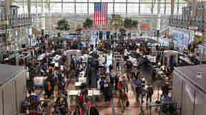 Passengers move through a main security checkpoint at the Denver International Airport on Nov. 22. Some airports are considering replacing government security screeners with private companies.