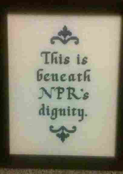 "A wall hanging reading ""This is beneath NPR's dignity."""
