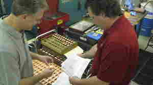 Brothers Michael (left) and Timothy Martens inspect copper machine parts on the factory floor.