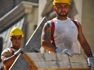 Construction workers lug building materials at a job site in New York's midtown Manhattan. While a number of industries added jobs in December, the construction sector lost 16,000.
