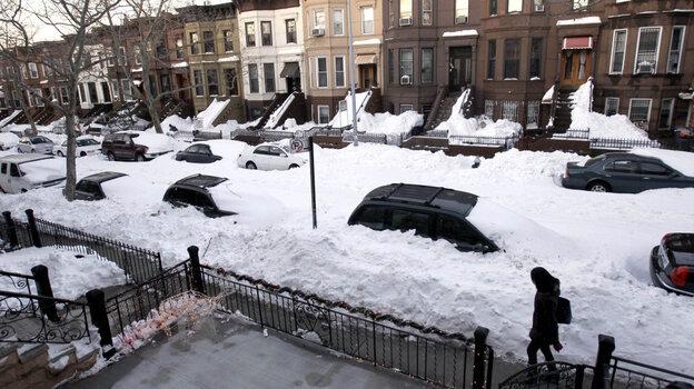 A pedestrian walks an unplowed street in Brooklyn days after a blizzard blew through in December.