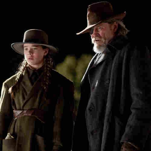 "Mattie Ross (Hailee Steinfeld) and U.S. Marshal Reuben ""Rooster"" Cogburn (Jeff Bridges) seek the man who gunned down her father in Joel and Ethan Coen's True Grit"