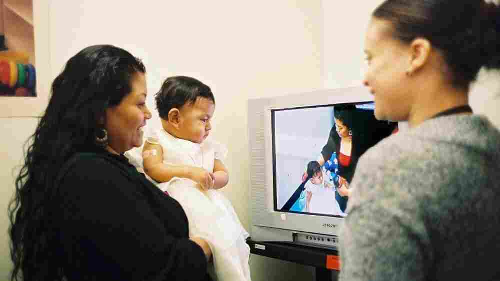 A mother watches a video taken of herself playing with her daughter for Bellevue Hospital's Video Interaction Project. Former hospital employee Brenda Woodford reviews the footage, offering positive feedback and areas for improvement.