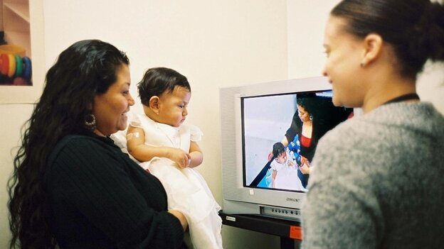 A mother watches a video taken of herself playing with her daughter for Bellevue Hospi
