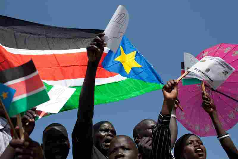 Secession supporters wave regional flags and placards upon the arrival of Sudan's President Omar Bashir in Juba on Tuesday. Bashir said he would celebrate the result of the week's referendum even if it resulted in secession.