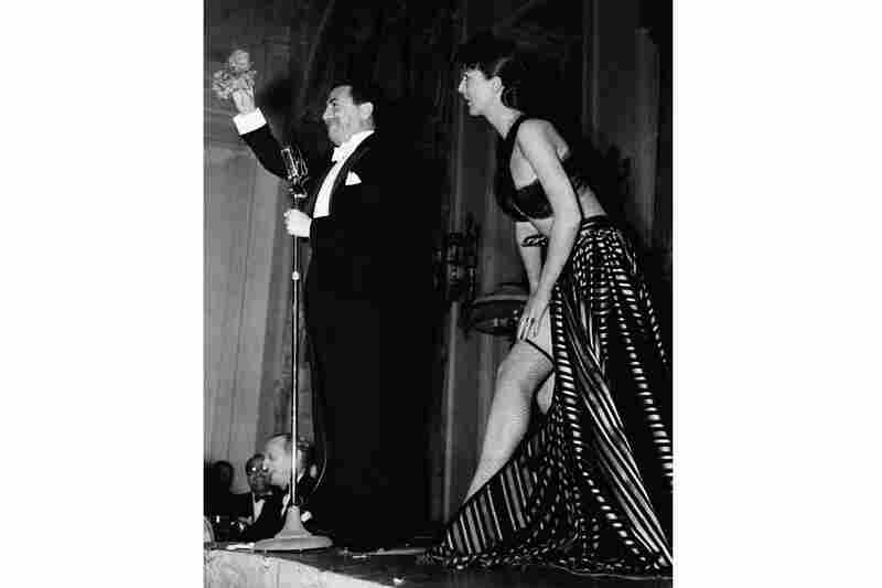 Gypsy Rose Lee delivers an $800 strip tease in New York at a benefit party for French war relief in 1940. The comedian Jack Pearl, left, acted as auctioneer, and movie actress Mary Pickford offered $400 for her to forget the strip tease, but the audience overruled the motion.