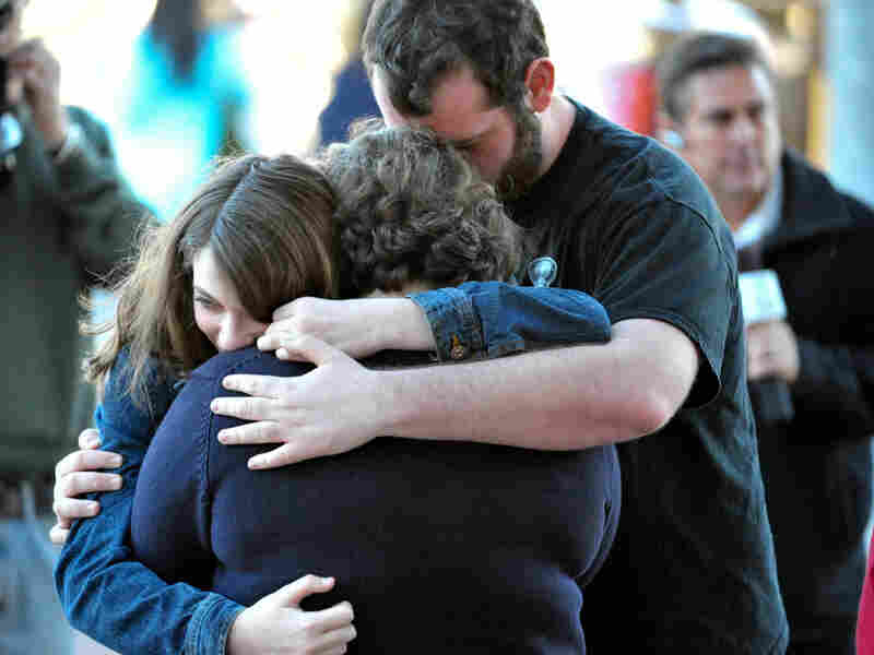 A Tucson family embraces outside Rep. Gabrielle Giffords' office after Saturday's shooting.