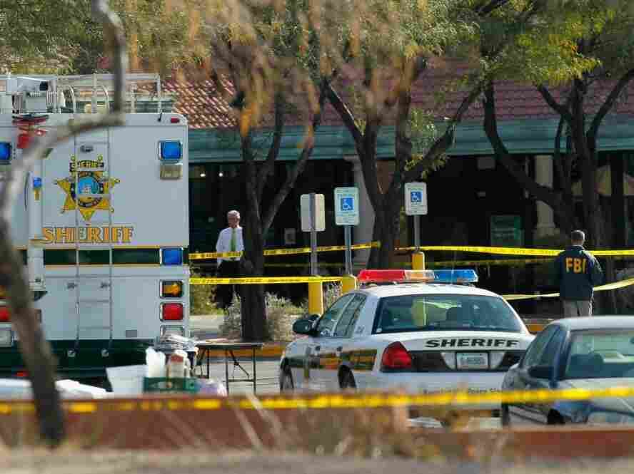 An FBI agent investigates the crime scene in front of the Safeway store in Tucson, Ariz., on Sunday. Hundreds of agents are working to understand what prompted 22-year-old Jared Loughner to allegedly go on a shooting rampage that killed six people and wounded Rep. Gabrielle Giffords (D-AZ).