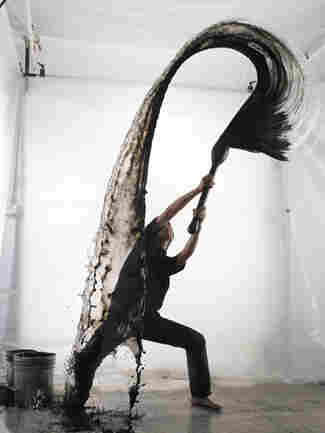 Artist Shinichi Maruyama throws a water and ink mixture in the studio while a camera captures his work.