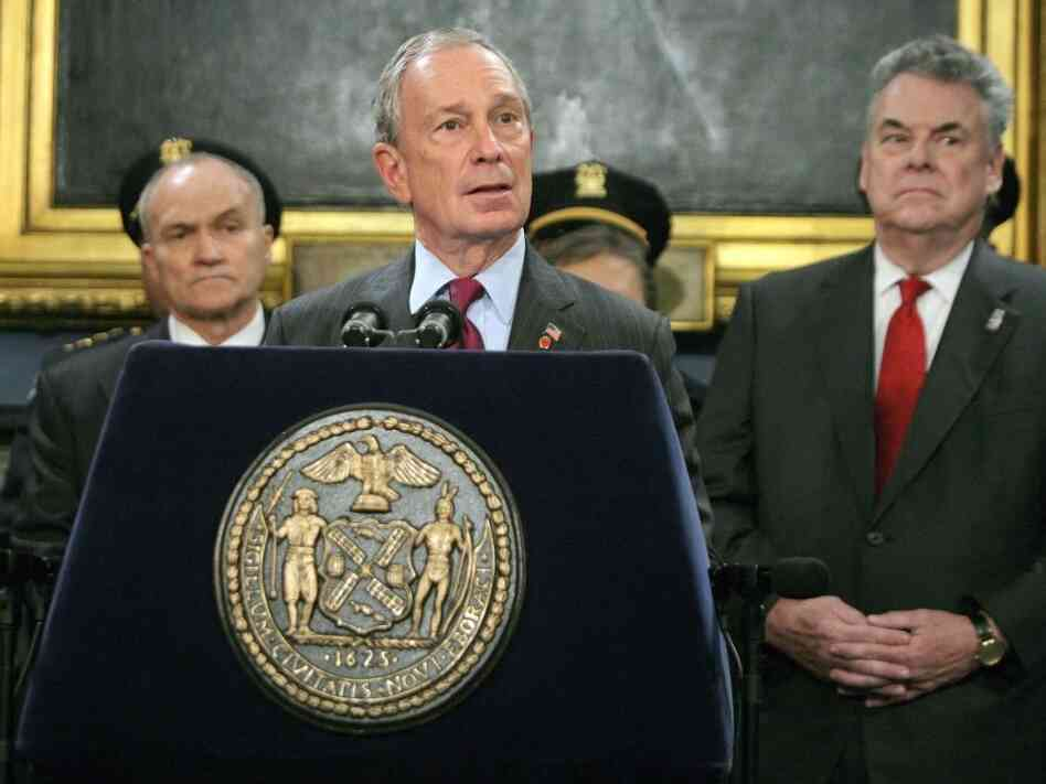New York City Mayor Mayor Michael Bloomberg talks to the news media as Rep. Peter King (R-NY) stands to the mayor's left.