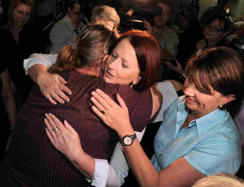 Australian Prime Minister Julia Gillard (center) hugs displaced resident Sandy Kiddle as Queensland Premier Anna Bligh looks on during a visit to an evacuation center in Bundaberg on Dec. 31. The Australian government estimated the cost of cleanup and rebuilding could be as high as $5 billion.