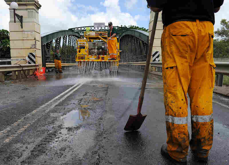 Firefighters clean mud from the Kennedy Bridge, which links the center of Bundaberg with its eastern suburbs.