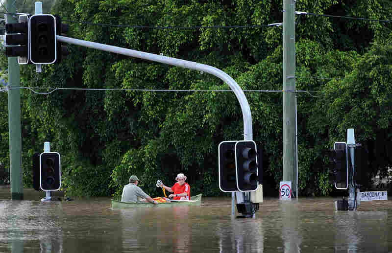 Residents navigate across their flooded suburb in Brisbane.