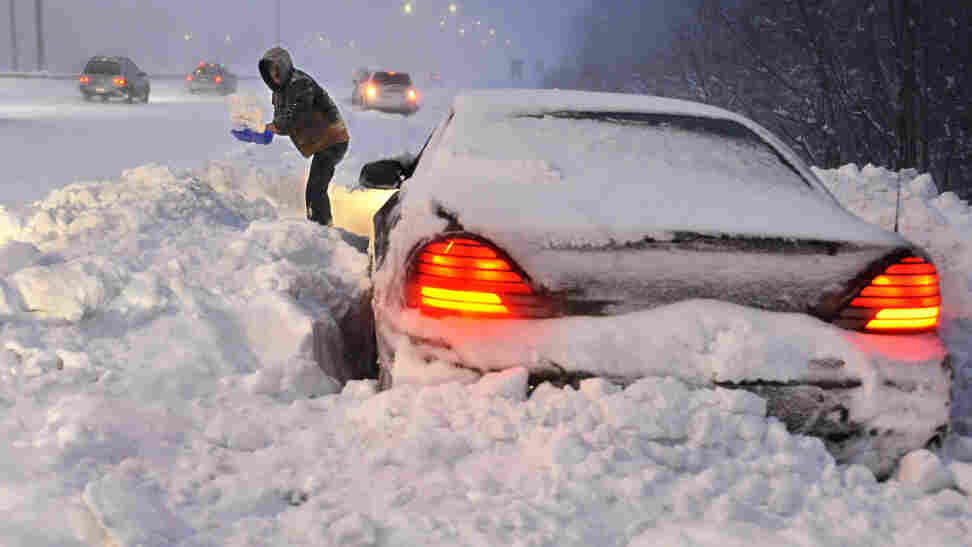 Roy Williams of Westfield, Mass., shovels snow in front of his vehicle on a merge ramp on Interstate 91 southbound in Windsor, Conn., Wednesday, Jan. 12, 2011.