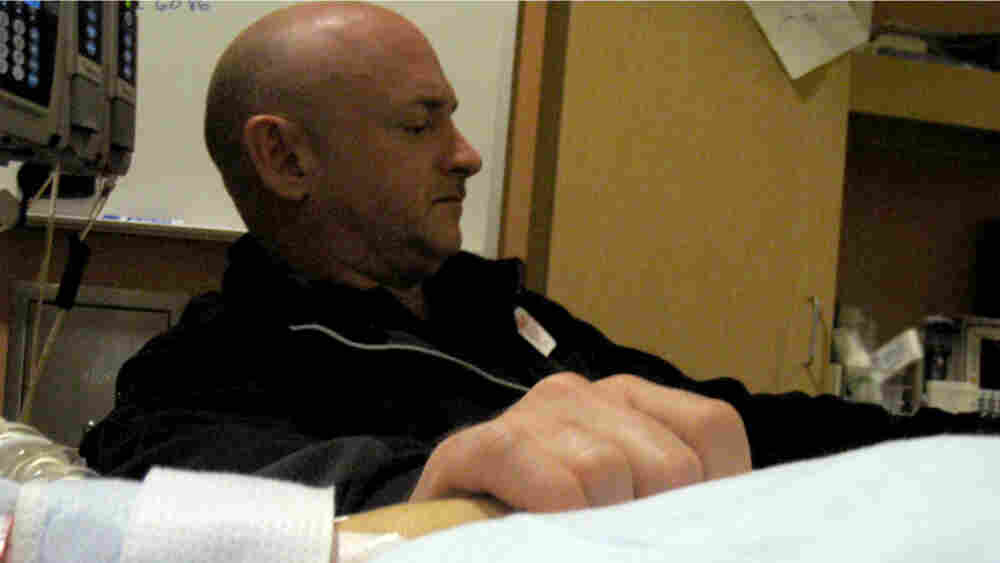 Mark Kelly holding the hand of his wife, Rep. Gabrielle Giffords, in her room at University Medical Center in Tucson on Sunday, Jan. 9, 2010.