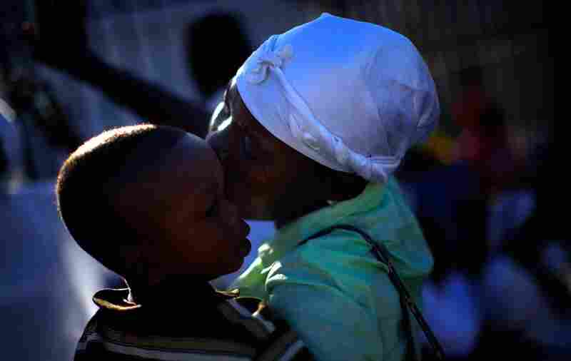 A Haitian woman holds her son in the front of the destroyed Catholic Church, Our Lady of Assumption, in downtown Port-au-Prince.