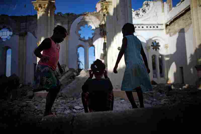 Girls play amid the rubble at Our Lady of Assumption Catholic Church on Wednesday.