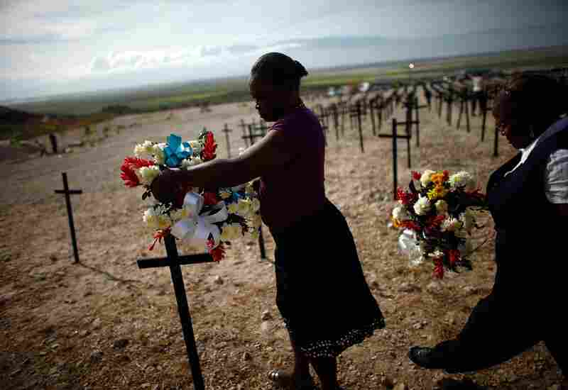 On Tuesday, women distribute wreathes at the mass graves near Titanyen, Haiti, where tens of thousands of people were buried.