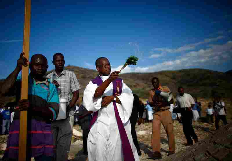 A priest spreads holy water at the site of the mass graves Tuesday.