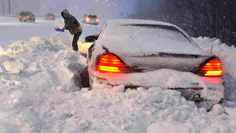 Roy Williams of Westfield, Mass., shovels snow in front of his vehicle on a merge ramp on Interstate 91 southbound during a winter storm Wednesday in Windsor, Conn.  Williams said a plow clearing the highway passed by and blocked him in.