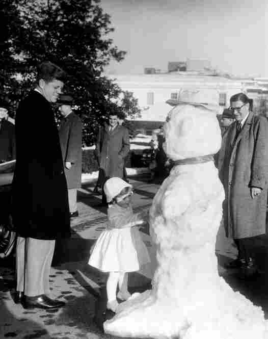 President  Kennedy watches his daughter Caroline inspect a snowman made for her on the White House driveway on Feb. 4, 1961.