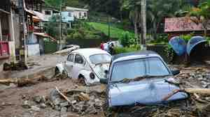 Cars sit in debris in a flooded street in Teresopolis, Rio de Janeiro state, Brazil, on Wednesday (Jan. 12, 2011).