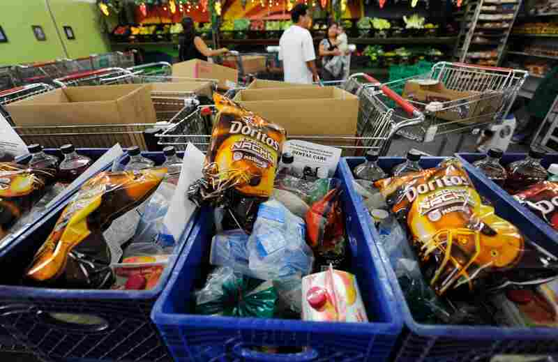 The World  Harvest food bank in Los Angeles readies carts full of groceries in September. While food banks leaders are trying to serve nutritional foods, the increasing demand has made it tough for them -- so they're still dishing out junk food and soda even if it does hungry people no favors.
