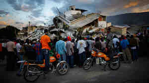 Haitians watch the L.A. County Search and Rescue working at a collapsed building in downtown Port-au-Prince, Jan. 16, 2010.