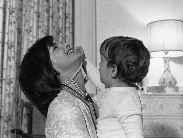 First lady Jacqueline Kennedy laughs as her son, John Jr., plays with her necklace in his White House bedroom in August 1962.