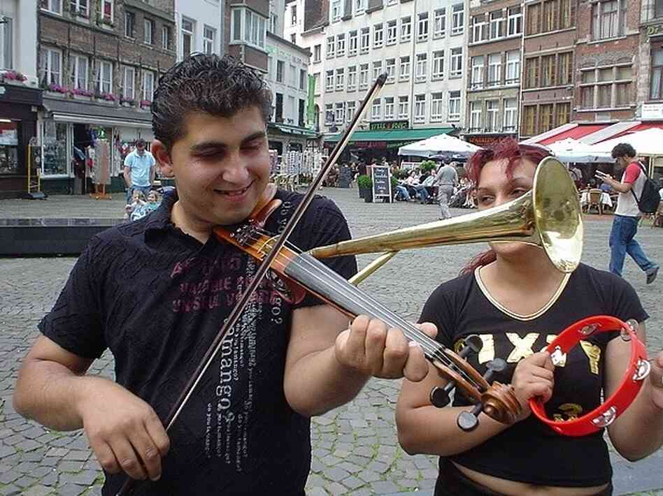 With a combination of a violin and trumpet in hand, this street musician shouldn't have a problem competing for customers with others.